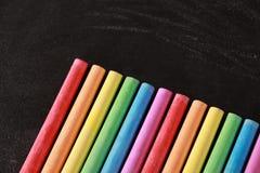 Craies colorées sur le tableau noir vide Photo stock