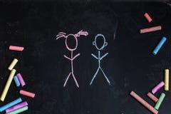 Craies colorées, tableau noir noir avec les dessins de la petite fille et garçon Photo stock