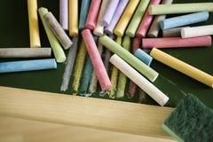 Craies multicolores et gomme de craie sur le tableau noir Image stock