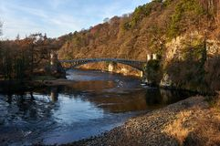 Craigellachie Bridge designed by Thomas Telford, on the river Spey. Craigellachie, Scotland: 17th December 2018 - A listed cast iron Craigellachie Bridge on the royalty free stock photography