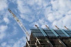 Crain contruction obramiał dużego miasto budynek z bufiastym obłocznym błękitem zdjęcia stock