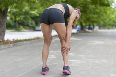 Cramp in leg calf during jogging. Woman holding sore leg muscle during running Stock Photography