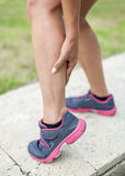 Cramp in leg calf during sports activity. Woman holding sore leg muscle Royalty Free Stock Photo