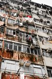 Cramped residential apartment building in the Asian city. Old rusty residential public housing apartment building with clothing hanging on outside window in stock photo