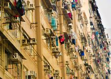 Cramped residential apartment building in the Asian city. Old rusty residential public housing apartment building with clothing hanging on outside window in royalty free stock photography