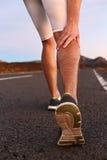 Crampes chez les veaux de jambe ou le veau d'entorse sur le coureur Photographie stock libre de droits