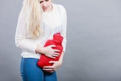 Crampes d'estomac de sentiment de femme tenant la bouteille d'eau chaude Image stock