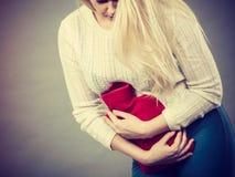 Crampes d'estomac de sentiment de femme tenant la bouteille d'eau chaude Photo stock