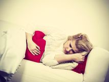 Crampes d'estomac de sentiment de femme se trouvant sur le cofa Photos libres de droits