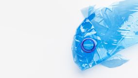 Save ocean concept. Crampled plastic bottle in fish shape on white background. Save ocean concept stock photography