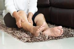 Crampo di gamba, donna senior che soffre dal dolore del crampo di gamba a casa, concetto di problema sanitario fotografie stock