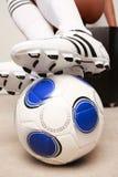 Crampons du football faisant un pas sur une boule Image stock