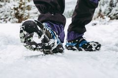 Crampons on hiking boots. Close up view on shoes on snowy path royalty free stock image