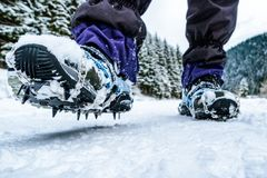 Crampons on hiking boots. Close up view on shoes on snowy path royalty free stock photos