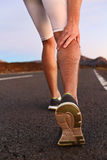 Cramps in leg calves or sprain calf on runner. Sports injury concept with running man outside Royalty Free Stock Photography