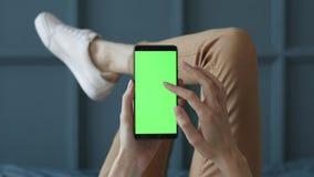 ?cran vert au t?l?phone portable de la jeune femme dans la chambre de lit ? la maison pour la cl? de chroma banque de vidéos