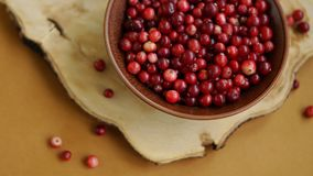 Cranberries in brown bowl on wooden desk Royalty Free Stock Images