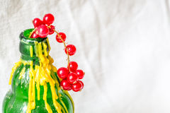 Cranberries and a green bottle with yellow wax. With white background Stock Photo