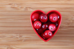 Cranberries in a heart bowl Royalty Free Stock Images