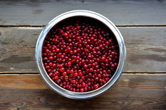 Cranberries. In metallic bowl, on wooden background. Shot made from above Stock Photo