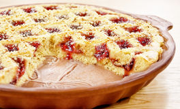 Cranberries pie. Sliced ​​cranberry cake in the form on wooden table Stock Photos