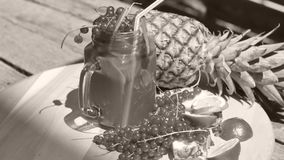 Jar of fresh pineapple juice. Cranberries and pineapple fresh fruit in a huge glass on a wooden table outdoors in the yard stock video footage