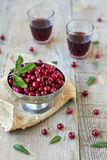 Cranberries and  red wine. Cranberries and two glasses of red wine on wooden table Stock Images