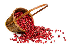 Cranberries spilling from wooden Basket. Сranberries spilling from wooden basket, isolated on white background Royalty Free Stock Images