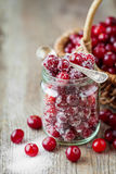 Cranberries with sugar in glass jar and basket with berries Stock Image