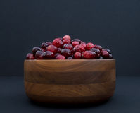 Cranberries in Turned  Wood Bowl against Black Background Stock Photos