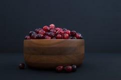 Cranberries w Drewnianym pucharze z jagodami Z pucharu Obrazy Royalty Free