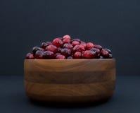 Cranberries w Obracającym Drewnianym pucharze przeciw Czarnemu tłu Zdjęcia Stock