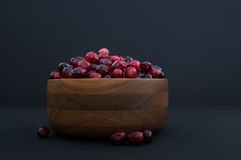 Cranberries in Wood Bowl with Berries Out of Bowl Royalty Free Stock Images