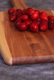 Cranberries on a wooden chopping board Stock Images