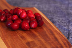 Cranberries on a wooden chopping board Royalty Free Stock Photos