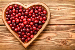 Cranberries on wooden tray on brown  wooden background. Royalty Free Stock Photo