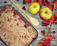 Cranberry Apple Cobbler. A 9x13 pan of cranberry apple cobbler with a wooden spoon filled with oatmeal and cranberries and apples and fall leaves framing the stock image