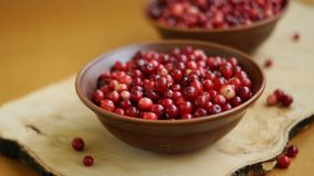 Cranberry in brown bowl on wooden desk Royalty Free Stock Photos