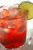 Cranberry Cocktail. Glass of ice cold cranberry cocktail with lime; crushed ice surrounding glass Stock Photography