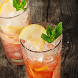 Cranberry cocktail with ice, mint, lemon and apple Royalty Free Stock Photos
