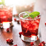 Cranberry cocktail with mint garnish. Close up photo of cranberry cocktail with mint garnish and lens flare Royalty Free Stock Photos