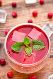 Cranberry cocktail with mint garnish. Cranberry cocktail with mint garnish on a wooden table Royalty Free Stock Image