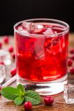 Cranberry cocktail with mint garnish. Cranberry cocktail with mint garnish on a wooden table Stock Image