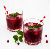 Cranberry cocktail with mint. Glasses with cranberry coctail on a old white wooden background Stock Photography