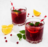 Cranberry cocktail with mint. Glasses with cranberry coctail on a old white wooden background Stock Photos