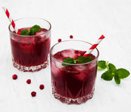 Cranberry cocktail with mint. Glasses with cranberry coctail on a old white wooden background Royalty Free Stock Image