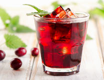 Cranberry cocktail with mint on a white wooden table. Royalty Free Stock Photography