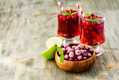 Cranberry cocktail with rime frosted berries. Cranberry drink with lime copy space selective focus Stock Image