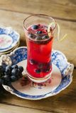 Cranberry color cocktail garnished with fresh grapes on a vinta. Vibrant red alcoholic beverage in a tall glass on rustic background royalty free stock photo
