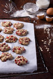 Cranberry cookies on a baking tray, cooking ingredients over rustic kitchen table. Crispy appetizers. Royalty Free Stock Photos
